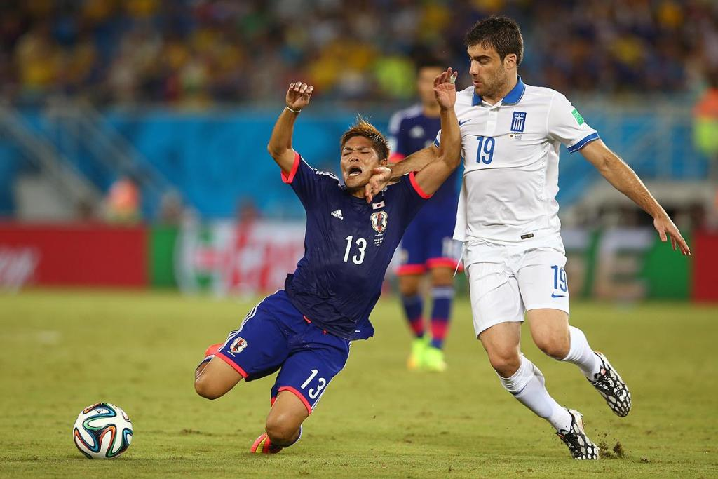 Yoshito Okubo of Japan is challenged by Sokratis Papastathopoulos of Greece