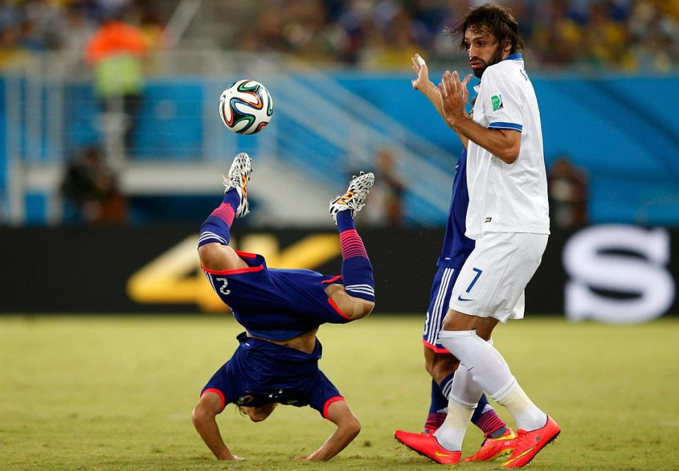 Greece's Giorgios Samaras commits a foul against Japan's Atsuto Uchida.
