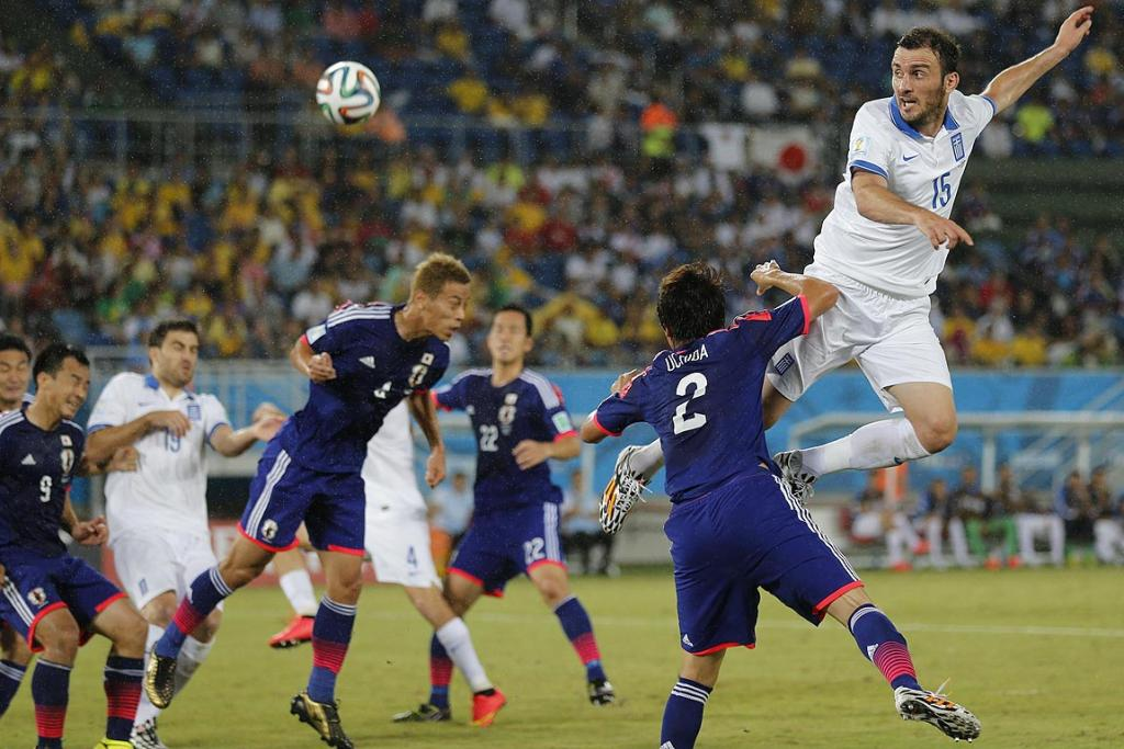 Greece's Vasilis Torosidis heads the ball against Japan.