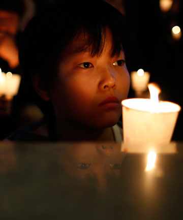 COMMEMORATING: A boy takes part in a candlelight vigil in Ansan, to commemorate the victims of the sunken passenger ship Sewol.