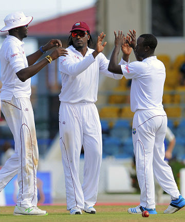GIMME FIVE: West Indies players Sulieman Benn, left, Chris Gayle, centre, and Kemar Roach the wicket of Ish Sodhi.