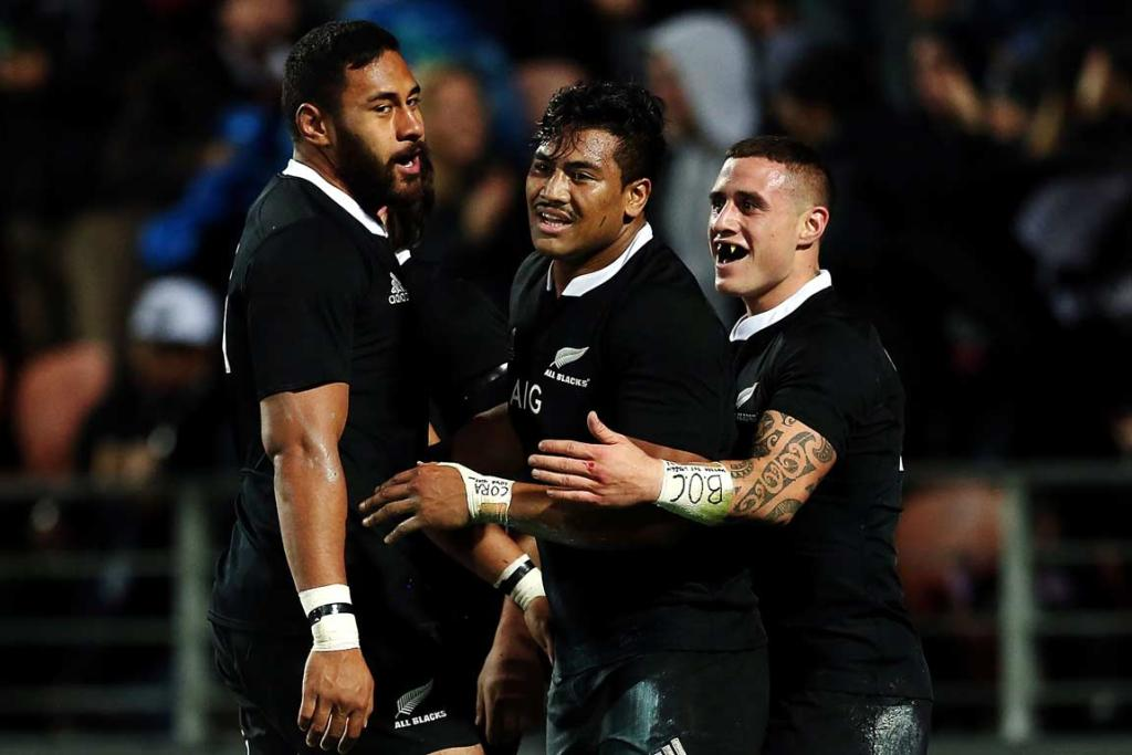 Patrick Tuipulotu (left) and TJ Perenara (right) congratulate Julian Savea after one of his three tries.