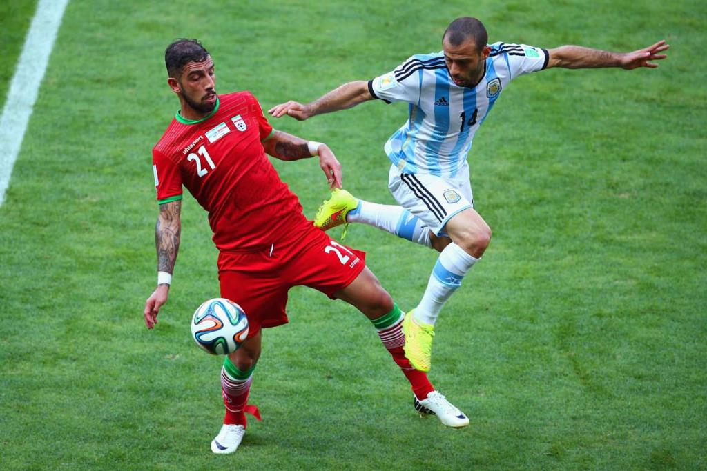 Argentina's Javier Mascherano (right) challenges Iran's Ashkan Dejagah for possession.