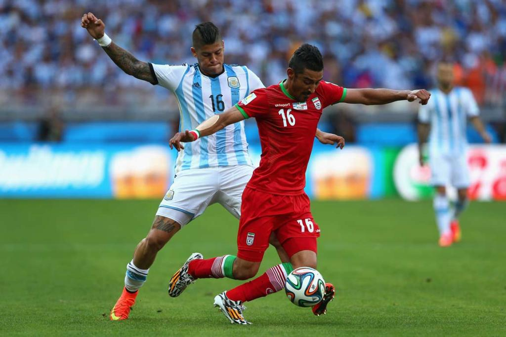 Argentina's Marcos Rojo trips Iran's Reza Ghoochannejhad as he attempts to get the ball.