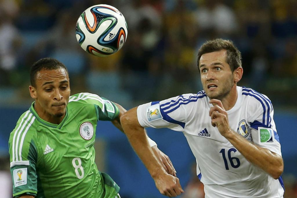 Nigeria's Peter Odemwingie and Bosnia's Senad Lulic contest possession.