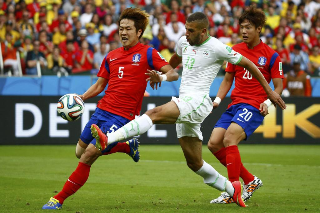 Algeria's Islam Slimani (centre) scores a goal next to South Korea's Kim Young-gwon (left) and Hong Jeong-ho during their World Cup Group H football match.