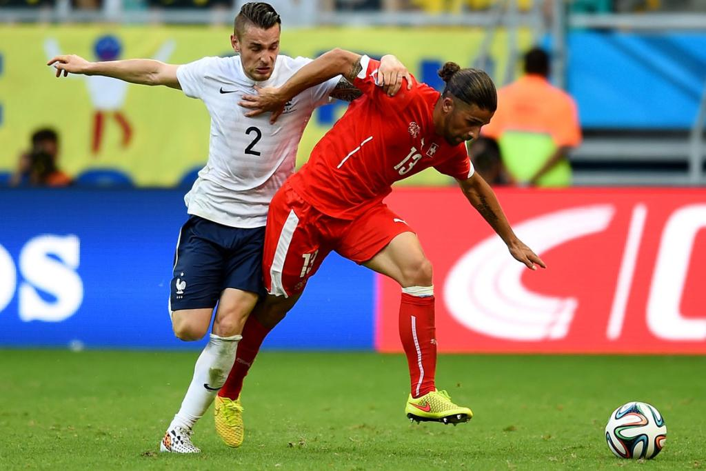 Ricardo Rodriguez of Switzerland fights off Mathieu Debuchy of France during the Group E match between Switzerland and France at Arena Fonte Nova in Salvador, Brazil.