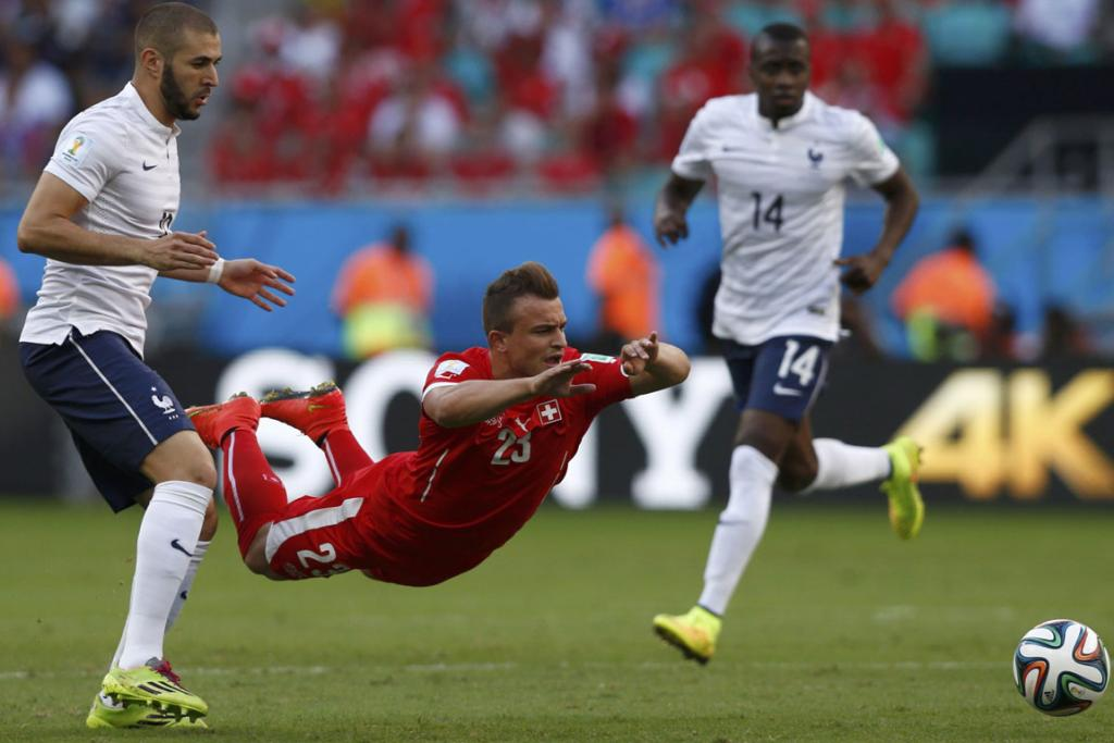 France's Karim Benzema (left) watches as Switzerland's Xherdan Shaqiri falls to the ground in front of him as they fight for the ball during their World Cup clash.