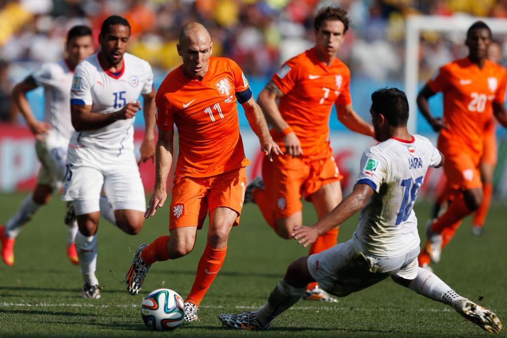 Arjen Robben of the Netherlands controls the ball as Gonzalo Jara of Chile gives chase during their World Cup clash in Sao Paulo, Brazil.