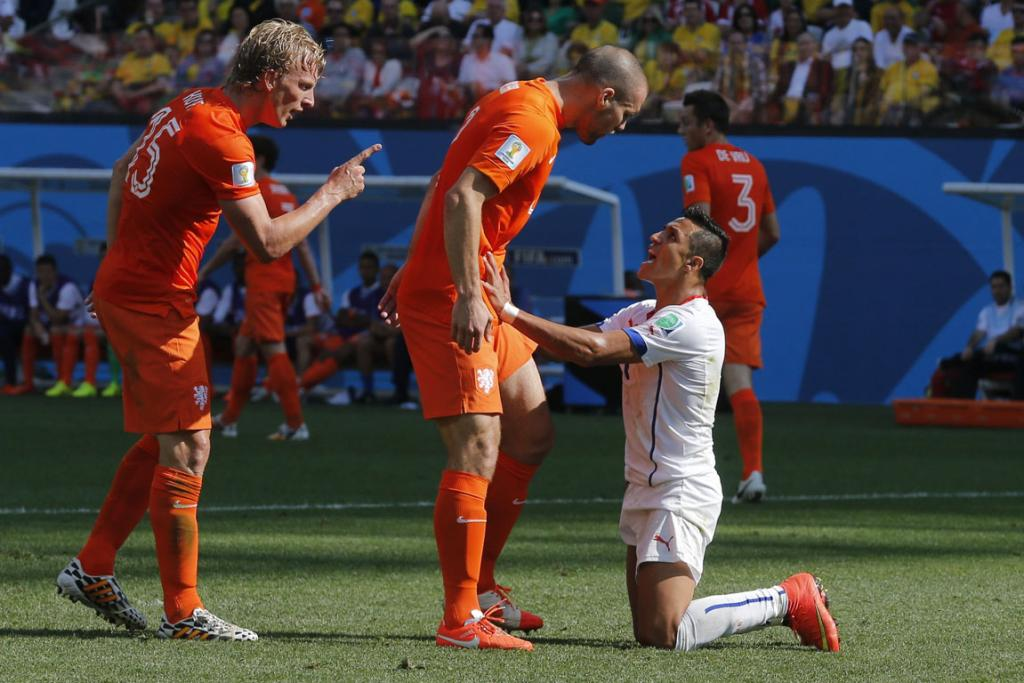 Chile's Alexis Sanchez (right) argues with Dirk Kuyt (left) and Ron Vlaar of the Netherlands during their 2014 World Cup Group B football match.
