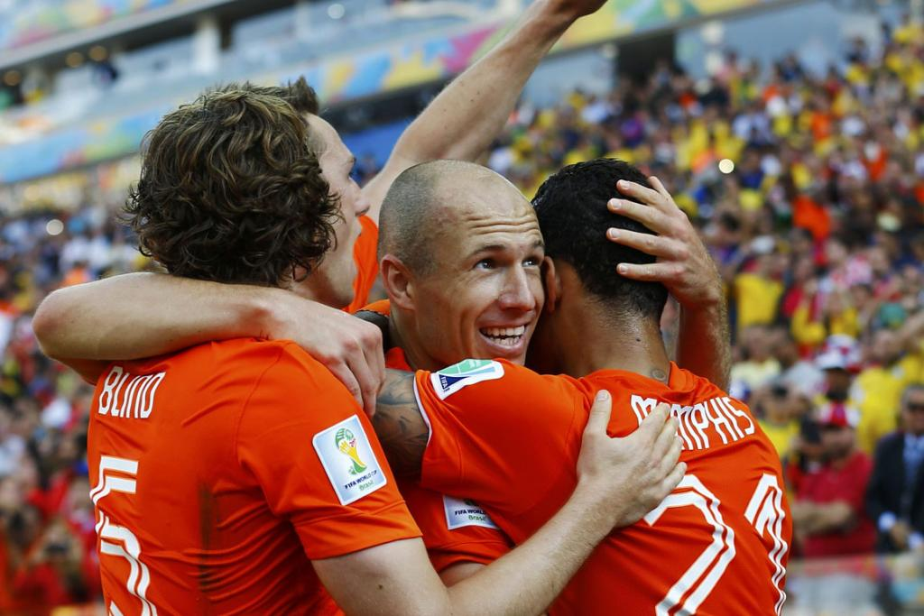 Memphis Depay of the Netherlands (right) celebrates after scoring a goal with teammates Arjen Robben (centre) and Daley Blind during their 2014 World Cup Group B football match against Chile.