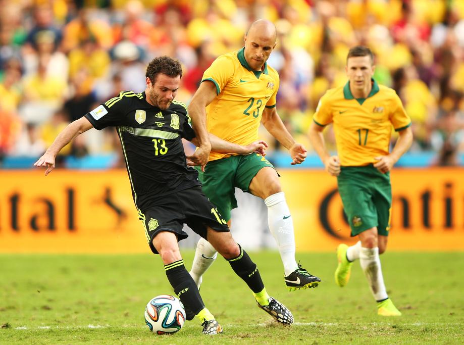 Spain midfielder Juan Mata is tracked by Australia's Mark Bresciano.