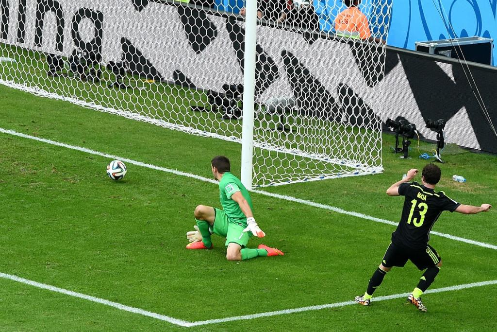 Juan Mata slots Spain's third goal through the legs of Socceroos goalkeeper Mathew Ryan.