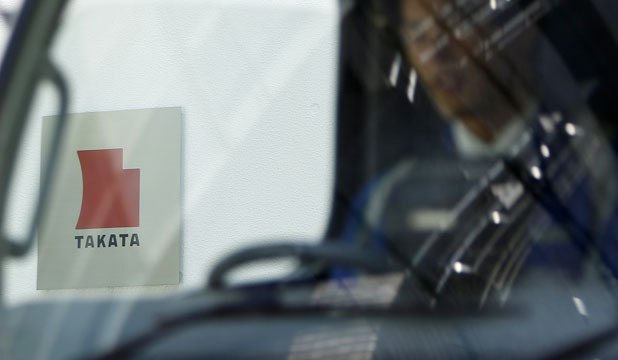 RECALL: A logo of Takata Corp is seen through a car window outside the company's headquarter building in Tokyo. Automakers are recalling millions of cars to replace airbags made by Takata that may have defective explosive charges in airbags that can send metal shrapnel flying at occupants during a crash.