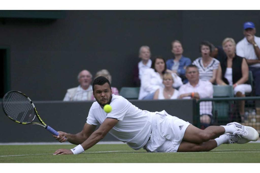 Jo-Wilfried Tsonga slips as he attempts to play a shot in a rain-delayed match against Jurgen Melzer.