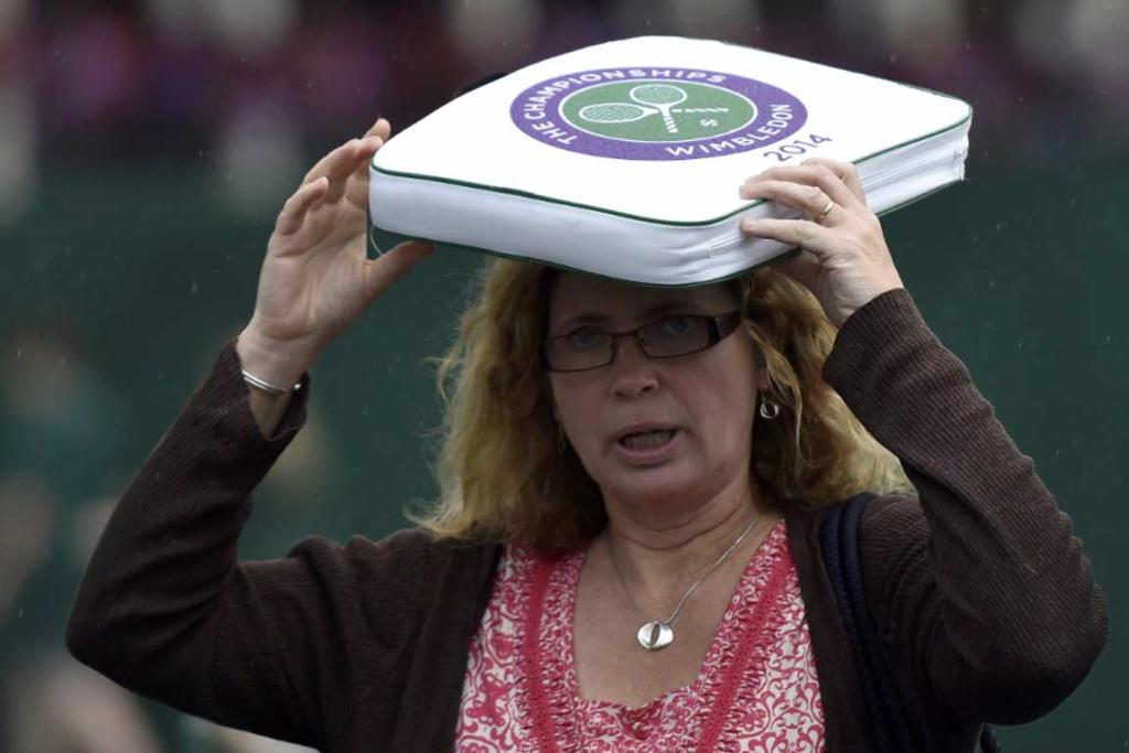 A tennis fan shelters herself from the rain with a seat cushion on day one.