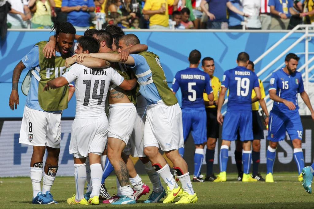 Uruguay players celebrate, while Italy players react, after their World Cup Group D football match at the Dunas arena in Natal.