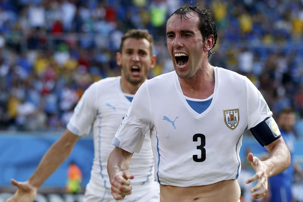 Uruguay's Diego Godin celebrates with team mate Christian Stuani (rear) after scoring a goal against Italy at the Dunas arena in Natal.