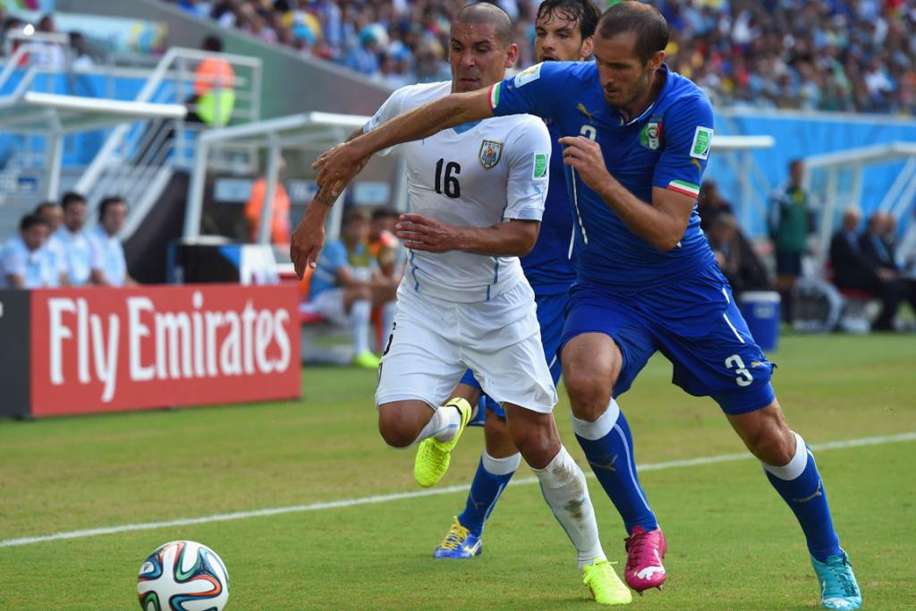 Giorgio Chiellini of Italy challenges Maximilliano Pereira of Uruguay during their Group D match.