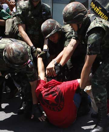 Soldiers detain a protester against military rule during a rally at a shopping district in central Bangkok.