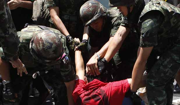UNREST: Soldiers detain a protester against military rule during a rally at a shopping district in central Bangkok.