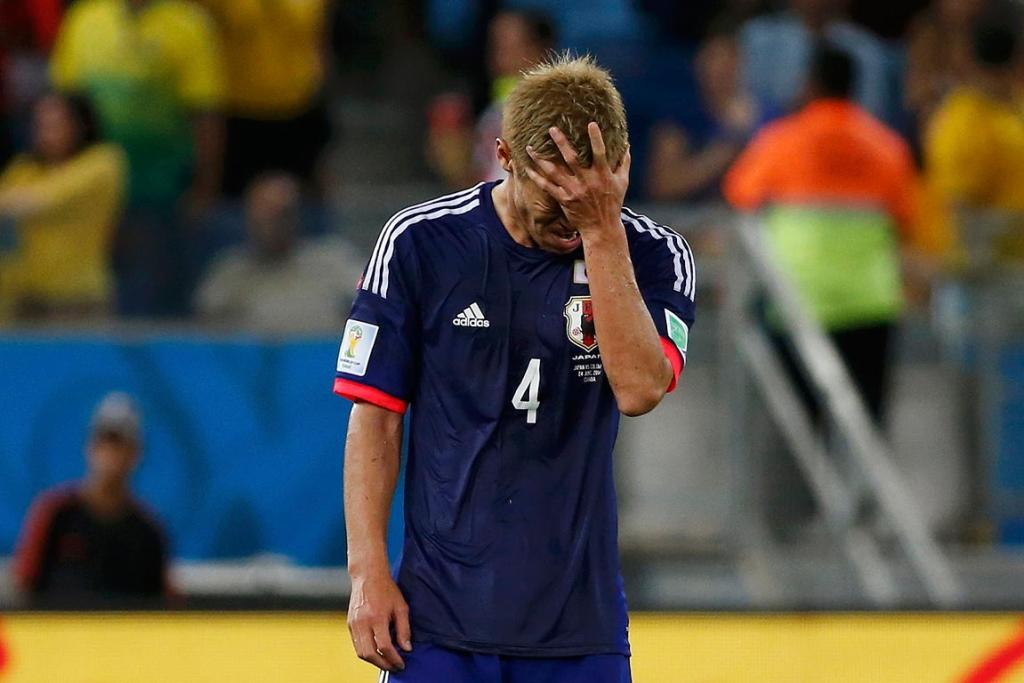Japan's Keisuke Honda reacts after Colombia scored their fourth goal.