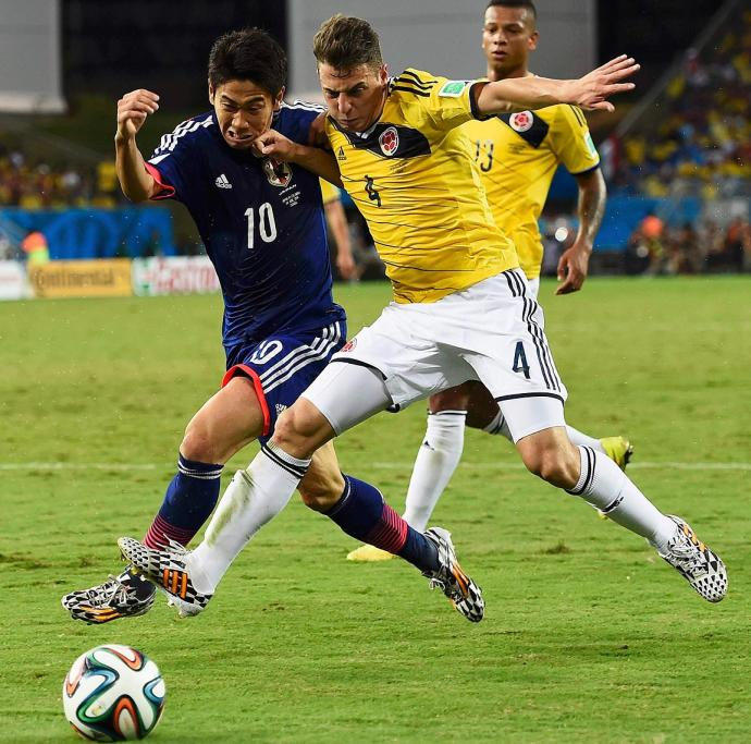 Colombia's Santiago Arias (R) fights for the ball with Japan's Shinji Kagawa