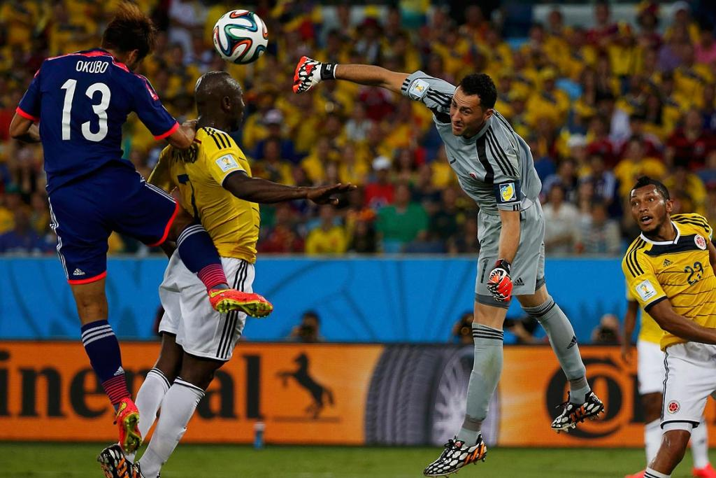 Colombia's goalkeeper David Ospina stops an attempt at goal as Japan's Yoshito Okubo jumps against Pablo Armero.
