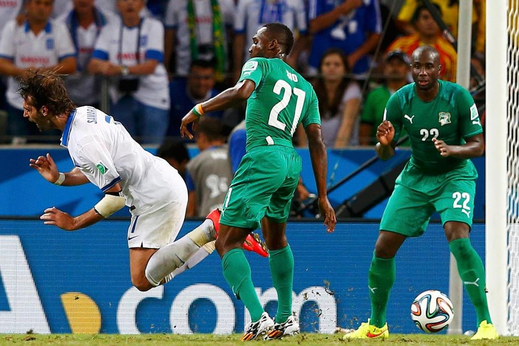 Greece's Giorgios Samaras goes down in the challenge of Ivory Coast's Giovanni Sio to win a penalty.
