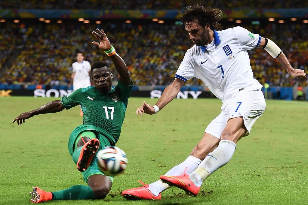 Serge Aurier of the Ivory Coast challenges Giorgos Samaras of Greece.