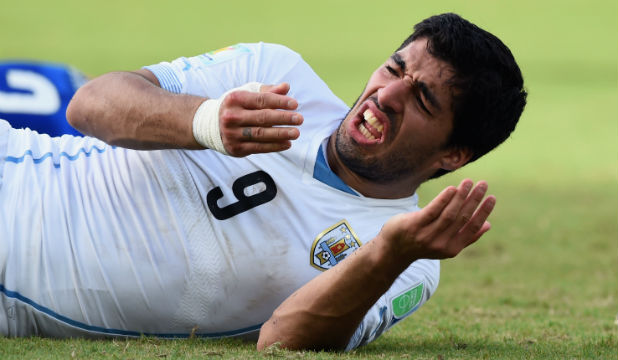 FLASHPOINT: Uruguay striker Luis Suarez falls to the ground after a clash with Italy defender Giorgio Chiellini during Uruguay's controversial 1-0 win.