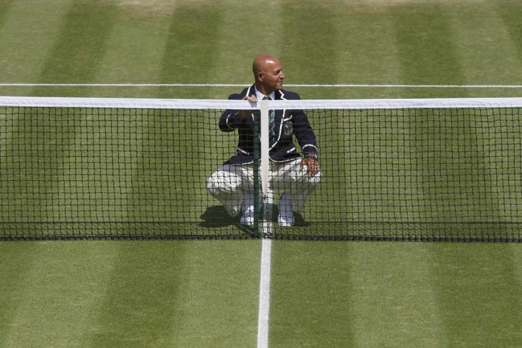 A tennis umpire checks the height of an outside court at Wimbledon.