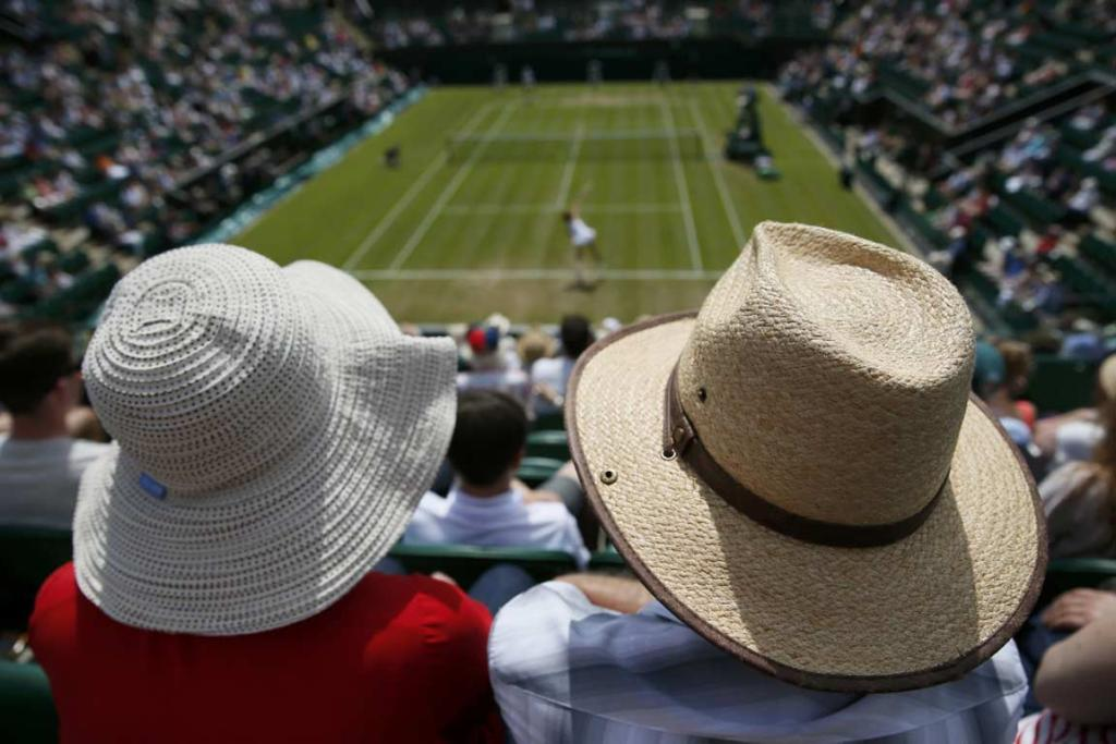Two tennis fans take in the action on day three at Wimbledon.