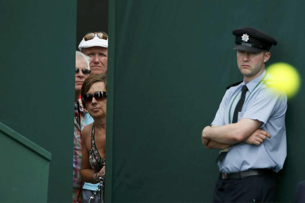 Wimbledon fans peer through a hole in the fence to catch a glimpse of Japan's Misaki Doi and Russia's Ekaterina Makarova.