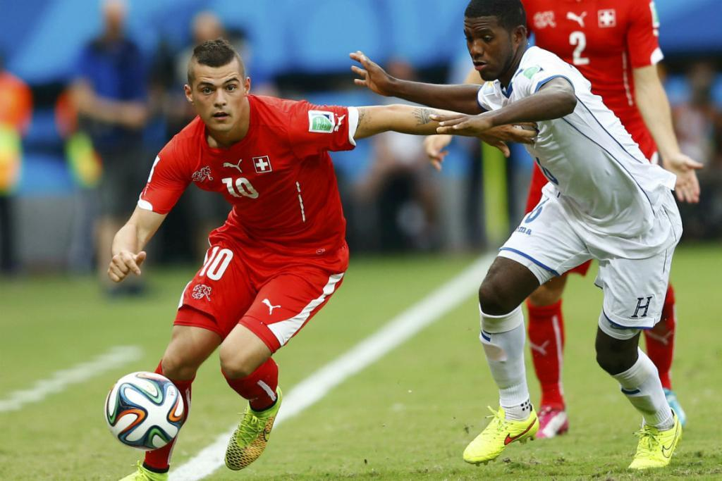 Switzerland's Granit Xhaka (left) is challenged by Hondruas defender Juan Carlos Garcia during their Group E match at the Amazonia arena in Manaus.