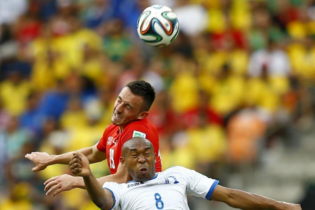 Switzerland's Josip Drmic (top) fights for the ball with Honduras midfielder Wilson Palacios.