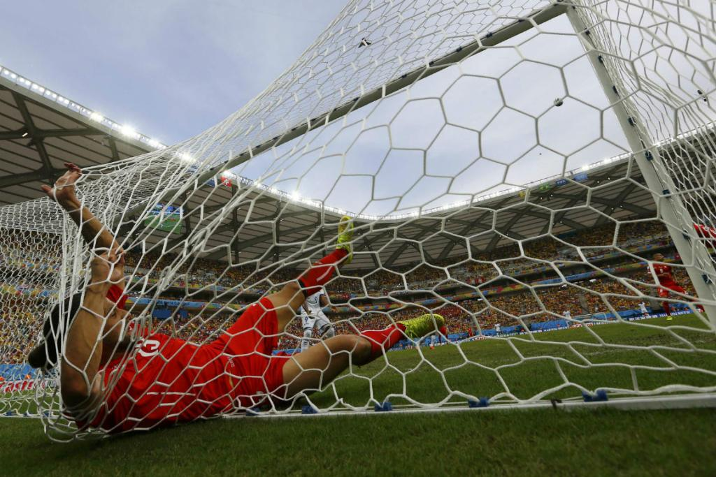 Switzerland's Ricardo Rodriguez falls into the net after clearing a shot by Jerry Bengston off the line.