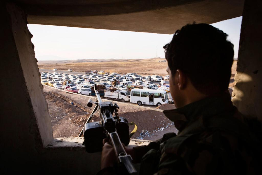 An Iraqi security forces member takes position as Mosul's refugees arrive in their vehicles at a camp for internally displaced people on the outskirts of Arbil in Iraq's Kurdistan region.