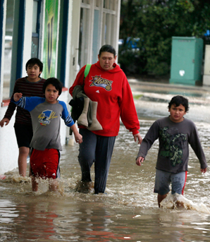 WET WEDNESDAY: Residents wade through flood water near Victory Square.