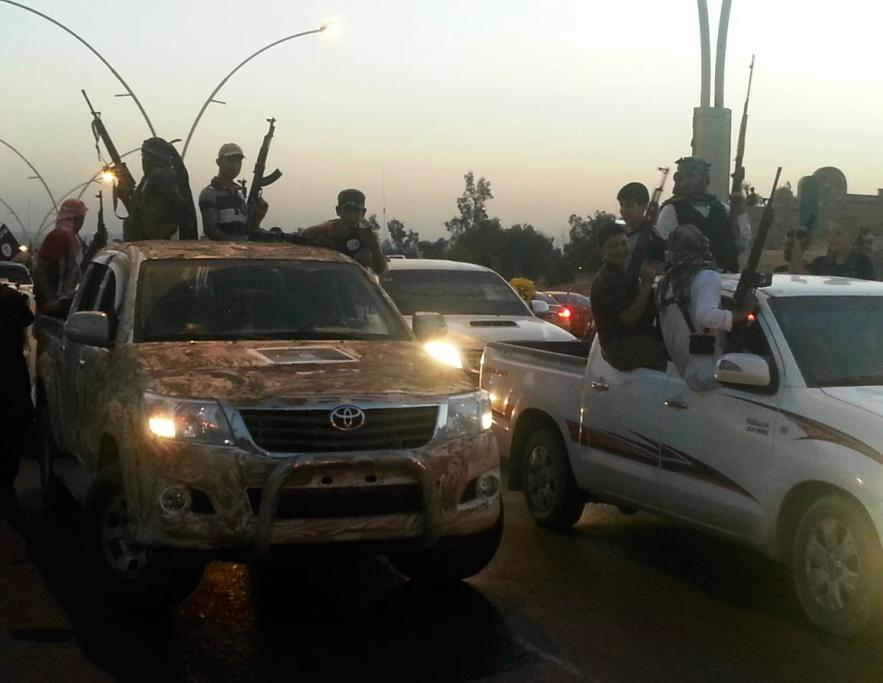 ISIL fighters celebrate with captured vehicles in Mosul.