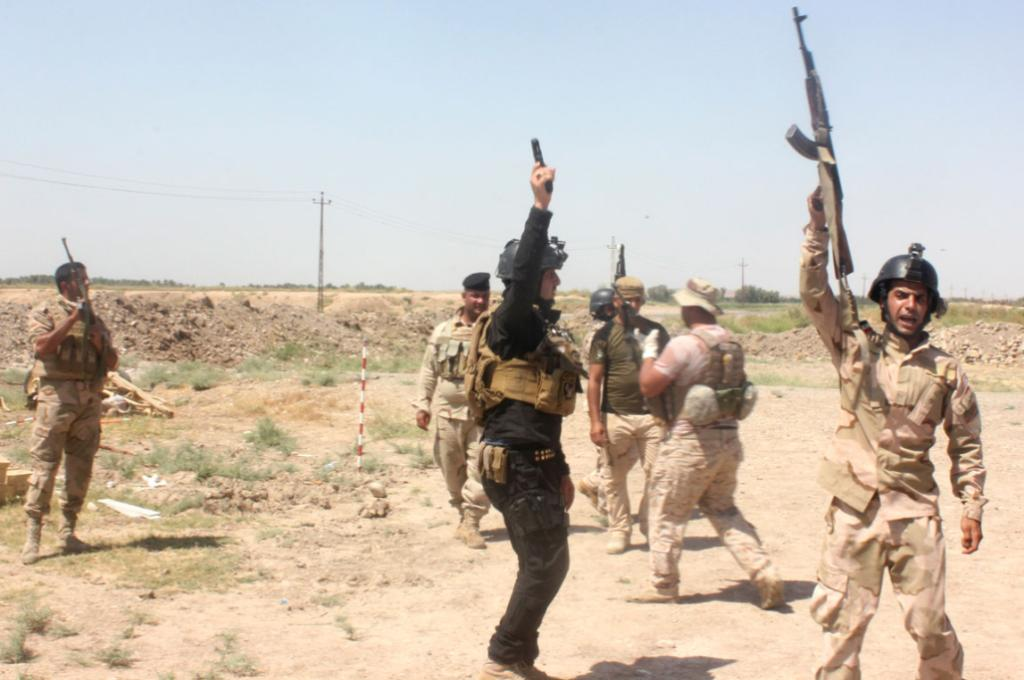 Members of the Iraqi security forces shout slogans as they carry weapons during clashes with ISIL in Muqdadiyah.