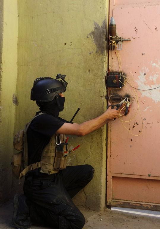 A member of the Iraqi Special Operations Forces prepares to open a door during a patrol in Ramadi.