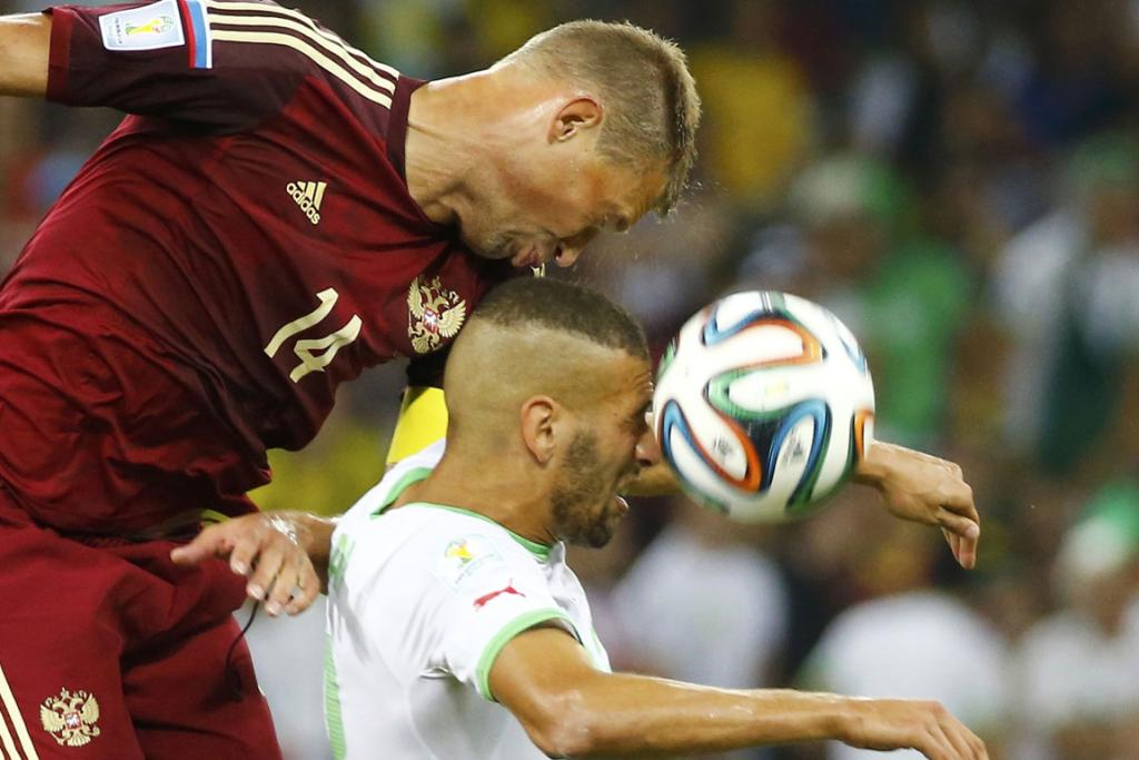 Russia's Vasili Berezutskiy (left) jumps for the ball with Algeria's Islam Slimani during their 1-1 draw at the Baixada arena in Curitiba.