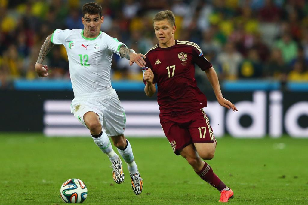 Carl Medjani of Algeria challenges Oleg Shatov of Russia during their World Cup Group H match.