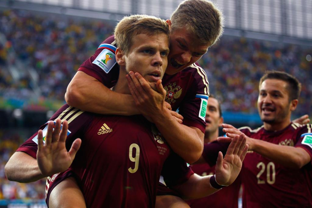 Alexander Kokorin of Russia celebrates scoring his team's goal against Algeria with teammate Oleg Shatov on his back.