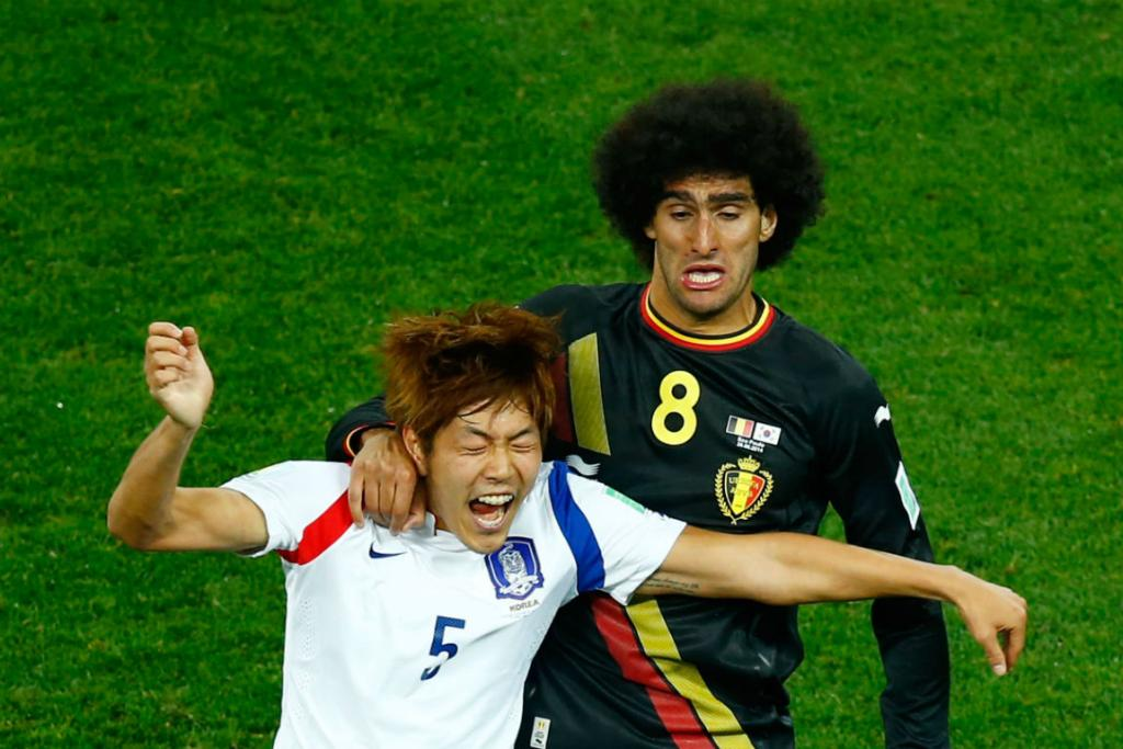 Belgium midfielder Marouane Fellaini challenges South Korea's Kim Young-Gwon during their Group H clash at Arena de Sao Paulo.