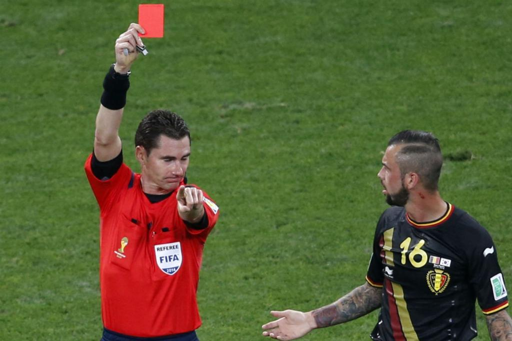 Referee Benjamin Williams shows Belgium's Steven Defour a straight red card for a two-footed tackle.