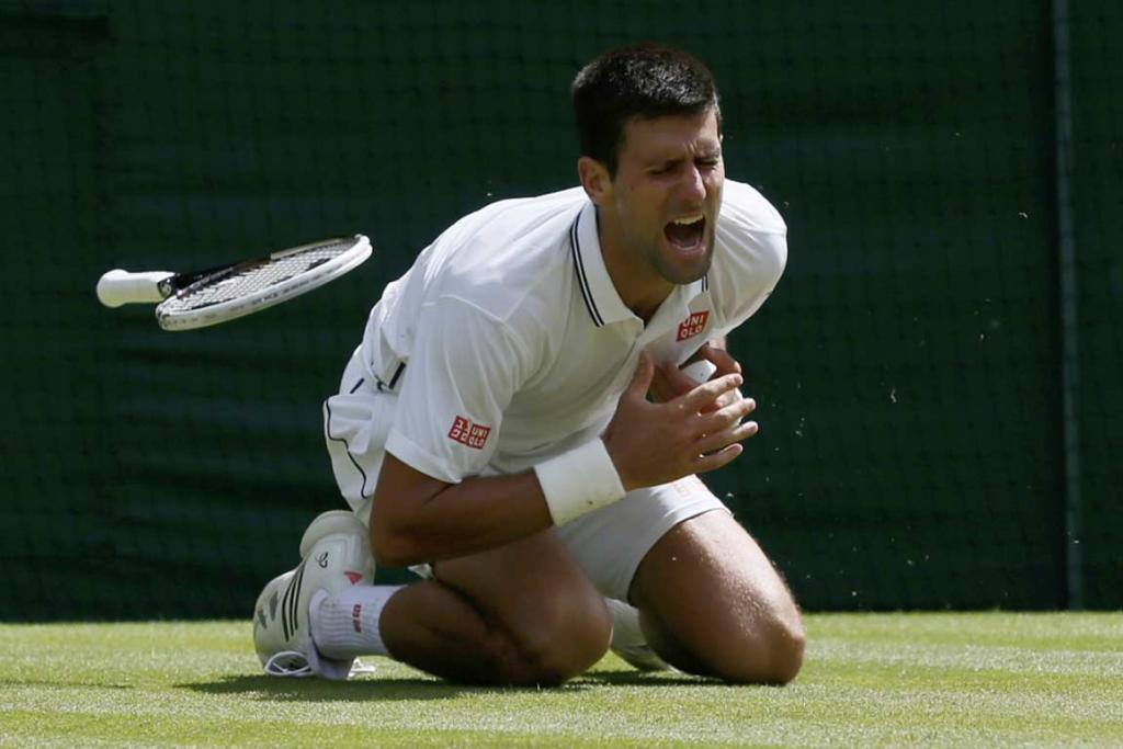 Novak Djokovic grimaces in pain after falling on his left shoulder diving for a shot.