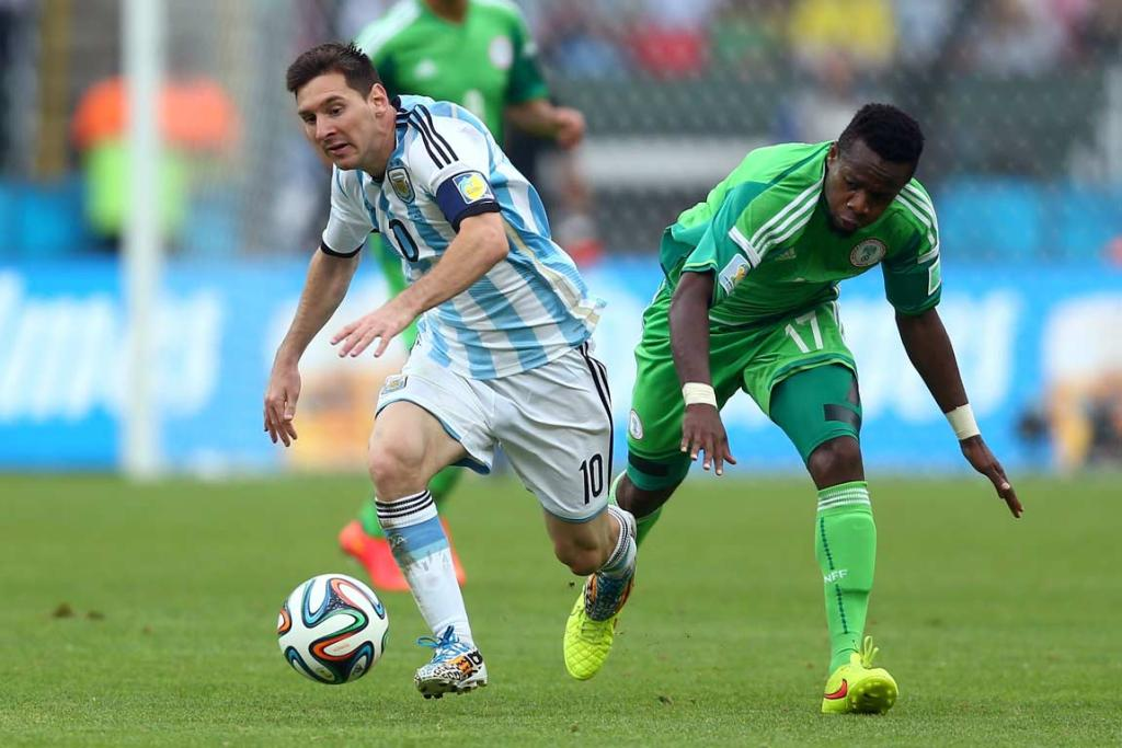 Lionel Messi collides with Nigeria's Ogenyi Onazi as he controls the ball in Argentina's group match win.