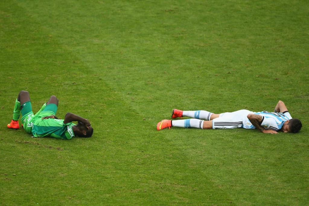 Juwon Oshaniwa of Nigeria and Ricardo Alvarez of Argentina lay on the ground after colliding.